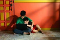 年轻亚洲孩子,兄弟或兄弟姐妹,有一台便携式计算机的在客厅 免版税库存图片