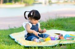 亚洲孩子画象使用在庭院里的 免版税库存图片