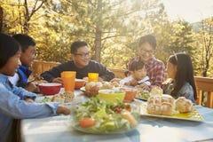 亚洲家庭吃午餐外面在甲板的一张桌上 库存照片