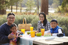 亚洲家庭在看对照相机的野餐桌上 免版税库存图片