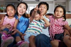 亚洲家庭坐一起看电视的沙发 免版税库存图片