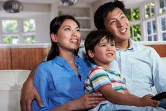 亚洲家庭坐一起看电视的沙发 图库摄影