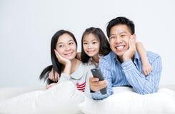 亚洲家庭坐看电视的沙发 免版税库存照片