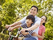 亚洲家庭骑马自行车在公园 库存照片