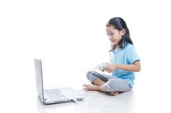亚洲小女孩打与便携式计算机的比赛和joystic 免版税库存图片