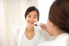 亚洲少妇刷牙她的牙愉快地 库存图片