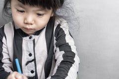 亚洲拿着有空间的女婴一只蜡笔文本的 免版税库存照片