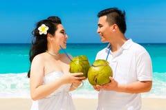 亚洲新娘和新郎在一个热带海滩 婚礼和蜜月 图库摄影