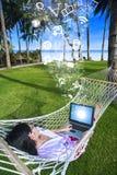 亚洲旅游说谎在使用膝上型计算机的网在海滩 图库摄影