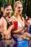 亚洲旅馆水池饮用的鸡尾酒的妇女 免版税库存照片