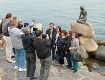亚洲游人参观小的美人鱼在哥本哈根 免版税库存图片