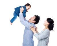 亚洲父亲投掷他的婴孩与微笑妻子 免版税库存照片