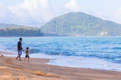 亚洲爸爸和儿子消费质量一起计时在海滩 库存照片
