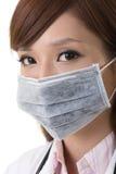 亚洲医生女服一个手术口罩 库存图片