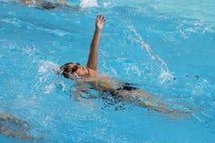 亚洲男孩后面爬行在游泳池游泳 免版税库存图片