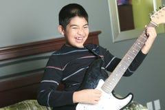 亚洲男孩戏剧吉他在他的卧室 免版税库存图片