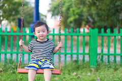 年轻亚洲男孩戏剧摇摆在操场的铁在下 库存照片