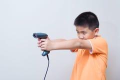 亚洲男孩目标用条形码扫描器做的一杆假枪 免版税图库摄影