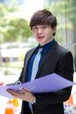 年轻亚洲男性商业主管待办卷宗 图库摄影