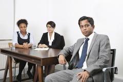亚洲男性画象与女性同事的在书桌的背景中在办公室 免版税库存照片