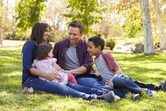 亚洲白种人混合的族种家庭坐草在公园 图库摄影