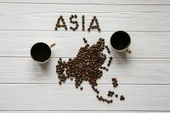 亚洲的地图放置在与两杯咖啡的白色木织地不很细背景的由烤咖啡豆制成 免版税库存图片