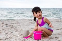 亚洲矮小中国女孩使用铺沙与海滩玩具 库存照片