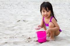 亚洲矮小中国女孩使用铺沙与海滩玩具 免版税库存照片