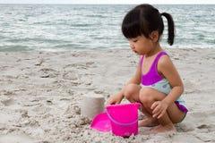 亚洲矮小中国女孩使用铺沙与海滩玩具 免版税库存图片