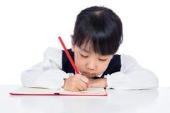 亚洲矮小的中国女孩文字家庭作业 免版税库存图片