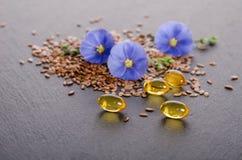 亚麻籽、秀丽花和油在盖帽在灰色背景 免版税库存照片