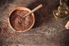 亚麻籽和亚麻仁油在玻璃水罐在一张木桌上 库存照片