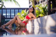 亚洲美丽的位于在池手段微笑的星期日晒日光浴的旅行热带妇女年轻人附近的比基尼泳装白种人懒人 说谎在水池附近的美丽的少妇 库存照片