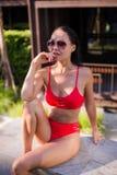亚洲美丽的位于在池手段微笑的星期日晒日光浴的旅行热带妇女年轻人附近的比基尼泳装白种人懒人 美丽的少妇在阴影坐在豪华旅馆在附近 图库摄影