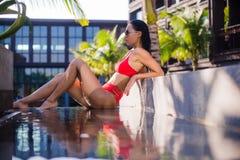 亚洲美丽的位于在池手段微笑的星期日晒日光浴的旅行热带妇女年轻人附近的比基尼泳装白种人懒人 说谎在水池附近的美丽的少妇 库存图片