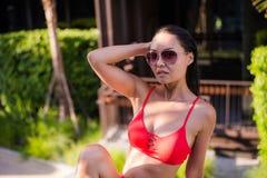 亚洲美丽的位于在池手段微笑的星期日晒日光浴的旅行热带妇女年轻人附近的比基尼泳装白种人懒人 美丽的少妇在阴影坐在豪华旅馆在附近 库存图片