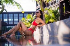 亚洲美丽的位于在池手段微笑的星期日晒日光浴的旅行热带妇女年轻人附近的比基尼泳装白种人懒人 说谎在水池附近的美丽的少妇 免版税库存照片