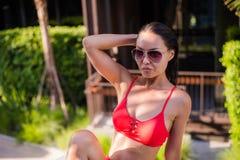 亚洲美丽的位于在池手段微笑的星期日晒日光浴的旅行热带妇女年轻人附近的比基尼泳装白种人懒人 美丽的少妇在阴影坐在豪华旅馆在附近 免版税图库摄影