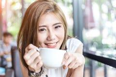 亚洲美丽的咖啡饮用的妇女 免版税图库摄影