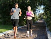 亚洲美丽的白种人夫妇横向户外人马拉松路运行运行培训的赛跑者赛跑者二名妇女 库存图片