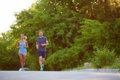 亚洲美丽的白种人夫妇横向户外人马拉松路运行运行培训的赛跑者赛跑者二名妇女 免版税库存照片
