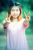 亚洲美好的女孩展示胜利标志 免版税库存照片