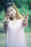 亚洲美好的女孩展示胜利标志 免版税库存图片
