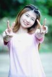 亚洲美好的女孩展示胜利标志 图库摄影