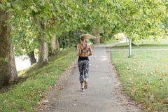 亚洲美好的白种人日种族健身跑步的马拉松混合模型室外公园连续体育运动夏天阳光培训妇女 库存图片