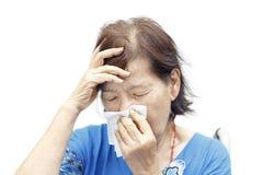 亚洲资深妇女头疼和寒冷 免版税库存照片