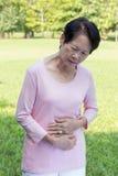 亚洲资深妇女stomachache 免版税库存图片