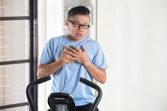 亚洲资深男性心脏痛苦 免版税库存照片