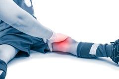亚洲足球运动员大腿痛苦,隔绝在白色背景  免版税库存照片