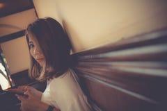 亚洲逗人喜爱的看照相机的女孩用途巧妙的电话 免版税库存图片